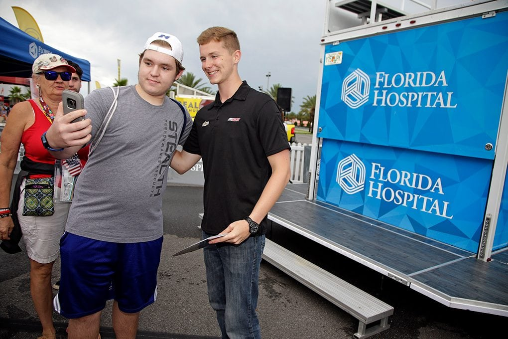 Matt Tifft poses for a selfie with a race fan at the Florida Hospital display in the Daytona International Speedway fan zone.