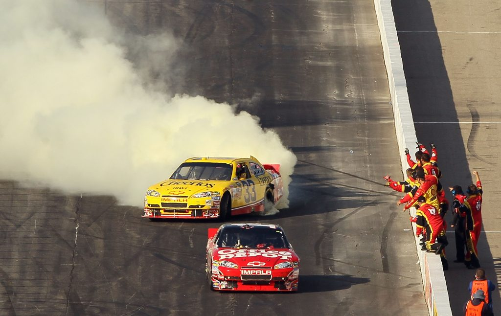 Clint Bowyer does a burnout as Tony Stewart coasts across the finish line out of fuel at New Hampshire Motor Speedway in 2010. (Photo by Elsa/Getty Images)